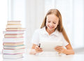 Girl with tablet pc and books at school education technology internet concept little student Stock Photo