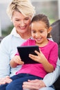 Girl tablet pc grandma cute little using with at home Stock Photography