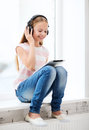 Girl with tablet pc and headphones at home leisure new technology music concept little Royalty Free Stock Photo