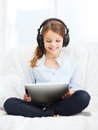Girl with tablet pc and headphones at home leisure new technology music concept smiling little computer Stock Images