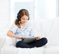 Girl with tablet pc and headphones at home leisure new technology music concept smiling little computer Stock Image