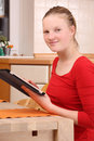 Girl with tablet pc young in kitchen working a computer Royalty Free Stock Photos