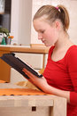 Girl with tablet pc young in kitchen working a computer Royalty Free Stock Photography