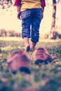 Girl take off her shoes child s foot learns to walk on grass leather reflexology massage relax in garden shallow depth of Royalty Free Stock Image