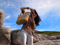 Girl taking a picture using camera happy cheerful young woman silver small boulders beach cape town south africa Royalty Free Stock Images