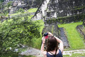 Girl taking pictures in tikal a while using her smartphone to take picture of the ruins of Royalty Free Stock Photo
