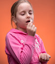 Girl taking pill on an orange background Royalty Free Stock Photo