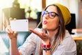 Girl taking selfie and sending air kiss. Royalty Free Stock Photo