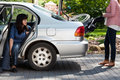 Girl taking wheelchair from car to provide mobility for disabled woman Royalty Free Stock Photos