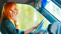 Girl talking on mobile phone while driving the car concept of danger young woman driver redhaired smartphone Royalty Free Stock Image