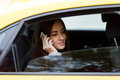 Girl talking on smartphone sitting in back seat of car Royalty Free Stock Photo