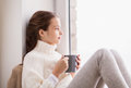 Girl with tea mug sitting at home window Royalty Free Stock Photo
