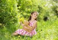 Girl with teddy cute little in pink dress is playing brown in green nature Royalty Free Stock Photo
