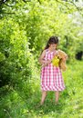 Girl with teddy cute little in pink dress is playing brown in green nature Stock Photos
