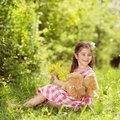 Girl with teddy cute little in pink dress is playing brown in green nature Royalty Free Stock Images