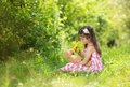 Girl with teddy cute little in pink dress is playing brown in green nature Stock Photo