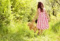 Girl with teddy cute little in pink dress is playing brown in green nature Royalty Free Stock Photography