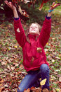 Girl teen playing with autumn leaves up in the air Royalty Free Stock Photo