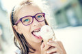 Girl. Teen. Pre teen. Girl with ice cream. Girl with glasses. Girl with teeth braces. Young cute caucasian blond girl wearing teet Royalty Free Stock Photo