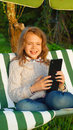 Girl of ten playing with tactile tablet happy sitting on the garden swing Royalty Free Stock Photography