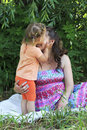 Girl tenderly kisses and hugs his mother little Stock Image