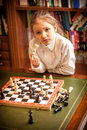 Girl thinking on move at chess portrait of Stock Photo