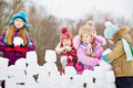 Girl with three little children build wall from snow bricks Stock Image