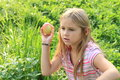 Girl throwing an apple little kid hairy blond Royalty Free Stock Photography