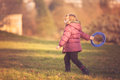 Girl throwing frisbee little in the park in autumn Stock Photos