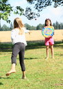 Girl throwing on a target little barefoot thorwing ball colorful holded by other Royalty Free Stock Photo