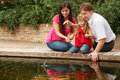 Girl throws stones in water with parents Royalty Free Stock Photos