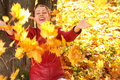 Girl throws yellow maple leaves Stock Photos