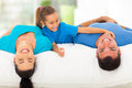 Girl tickling father cute little her while family lying on bed at home Royalty Free Stock Images