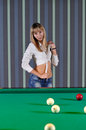 The girl ties a shirt in the billiard room Royalty Free Stock Photos