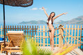 Girl on tiptoes enjoys sun and sea travel Royalty Free Stock Image