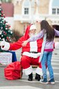 Girl about to embrace santa claus rear view of in courtyard Royalty Free Stock Images