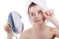 The girl in a towel after a shower pastes eyelashes looking in a mirror it is isolated on white background Royalty Free Stock Photo