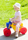Girl on toy motorcycle Stock Photos