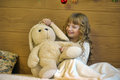 Girl with a toy rabbit on the bed Royalty Free Stock Photo