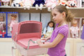 Girl in a toy store with many dolls purchased buggy Royalty Free Stock Photos