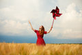 Girl with toy wind turbine redhead at wheat field Royalty Free Stock Image