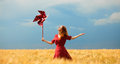 Girl with toy wind turbine redhead at wheat field Stock Image