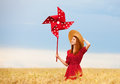 Girl with toy wind turbine redhead at wheat field Royalty Free Stock Photo