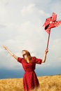Girl with toy wind turbine redhead at wheat field Royalty Free Stock Photos