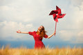 Girl with toy wind turbine redhead at wheat field Stock Images