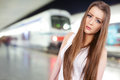 Girl at train station cute with oncoming in background Stock Image