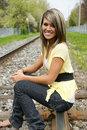 Girl on the train tracks a beautiful smiling model sitting Stock Images