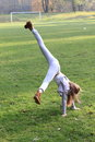 Girl training cartwheel exercising little kid in grey clothes and brown shoes on green grass of football stadion Stock Images