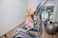 Girl training in the gym little blond equipment Royalty Free Stock Image