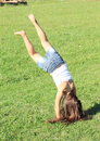 Girl training handstand exercising barefoot with long hair in white t shirt and blue shorts a on green grass Royalty Free Stock Photos